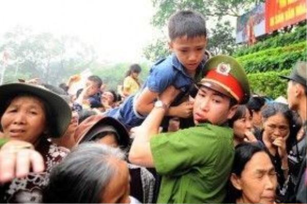 Để bảo vệ các em nhỏ, lực lượng chức năng phải len vào đám đông để bế hàng trăm em lên phía trước.