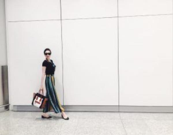 """Trong chuyến du lịch đến Hồng Kông, nữ ca sĩ """"Con tim anh nằm đâu"""" Bảo Thy khiến các fan yêu thích khi chọn trang phục dạo phố nổi bật nhưng dễ phối hợp từ kiểu áo thun trơn màu đi cùng chiếc quần suông chi tiết kẻ sọc nhiều màu, kèm giày bệt, cặp kính đen sành điệu và chiếc túi xách oversize của thương hiệu Céline."""