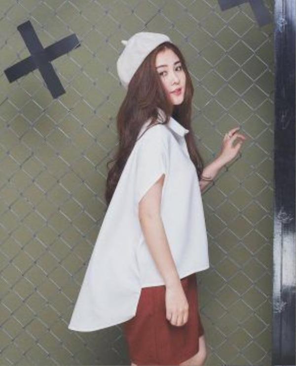 Đôi khi lại nữ tính hơn với áo sơmi vạt đuôi tôm điệu đà cùng chân váy. Chiếc mũ nồi màu nude đội đầu làm điểm nhấn cho cả set đồ.