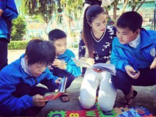 Đôi khi cô chọn một chiếc quần jean trắng với áo thun len cổ tim, bình dị dạy các bạn nhỏ đọc chữ.