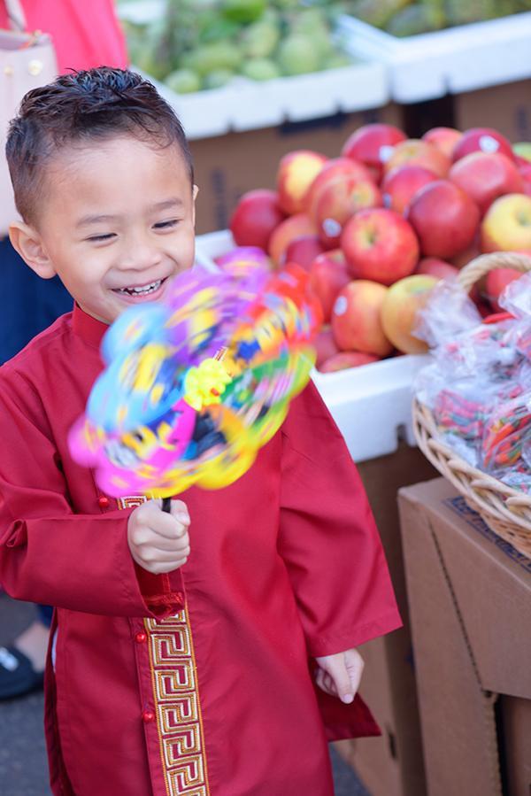 Cậu bé thích thú khi được dẫn đi chơi chợ Tết ở Mỹ.