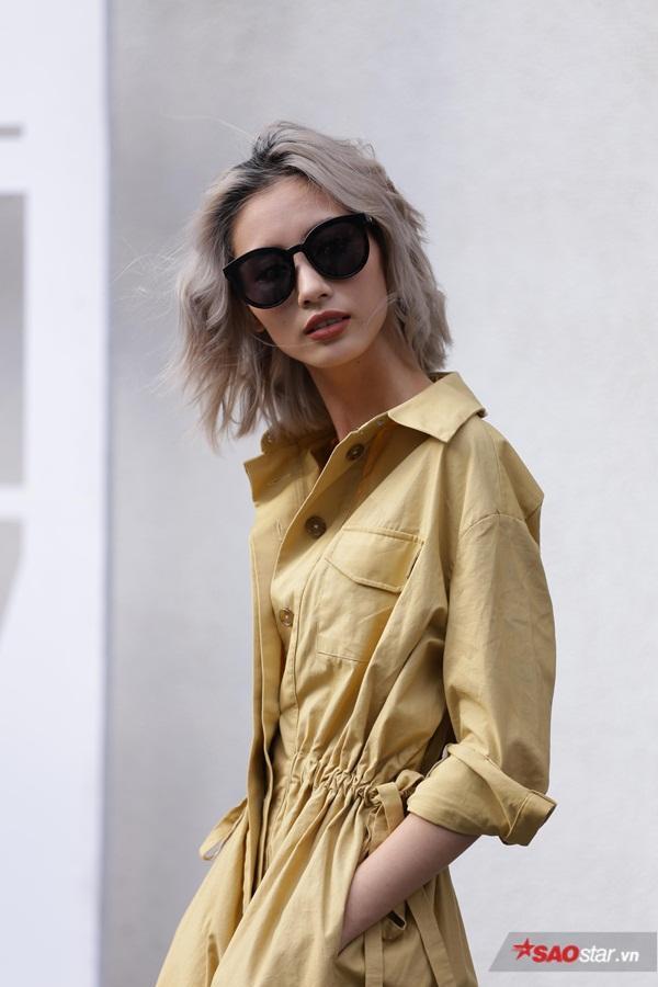 Người mẫu Hằng Nguyễn đơn giản với chiếc váy màu khaki chít eo khỏe khoắn. Mái tóc bạch kim tạo nên thương hiệu cho cô nàng này.