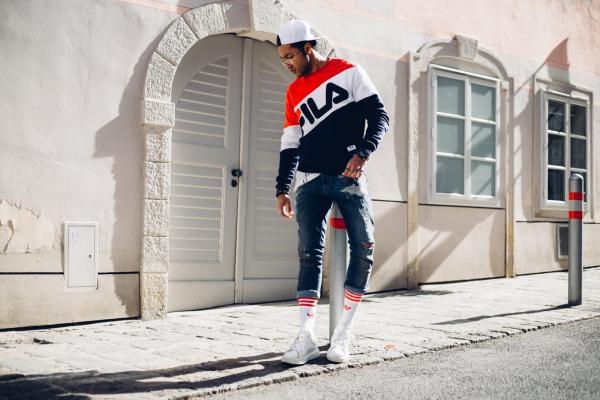 Màn chào sân ấn tượng dành cho anh chàng kết hợp sweater FILA với skinny jeans đơn giản, tinh ý mang tất cao ton-sur-ton với giày nhằm tăng thêm chiều dài cho đôi chân lại vừa nhấn nhá hài hòa cùngmàu sắc đặc trưng củathương hiệu.