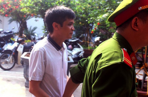 Công an dẫn giải bị cáo Nguyễn Đình Lê ra tòa (Ảnh: Thương hiệu và Công luận)