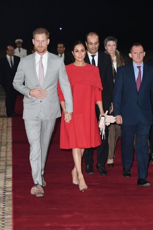 Meghan nổi bật với đầm đỏ rực rỡ đến từ thương hiệu Valentino. Đây là lần hiếm hoi nữ công tước xứ Sussex không diện đồ ôm sát mà mặc một chiếc đầm thoải mái. Nhưng việc Meghan vẫn trung thành với đôi giày cao gót, điều không được khuyến khích với phụ nữ mang thai ở tháng thứ 7.