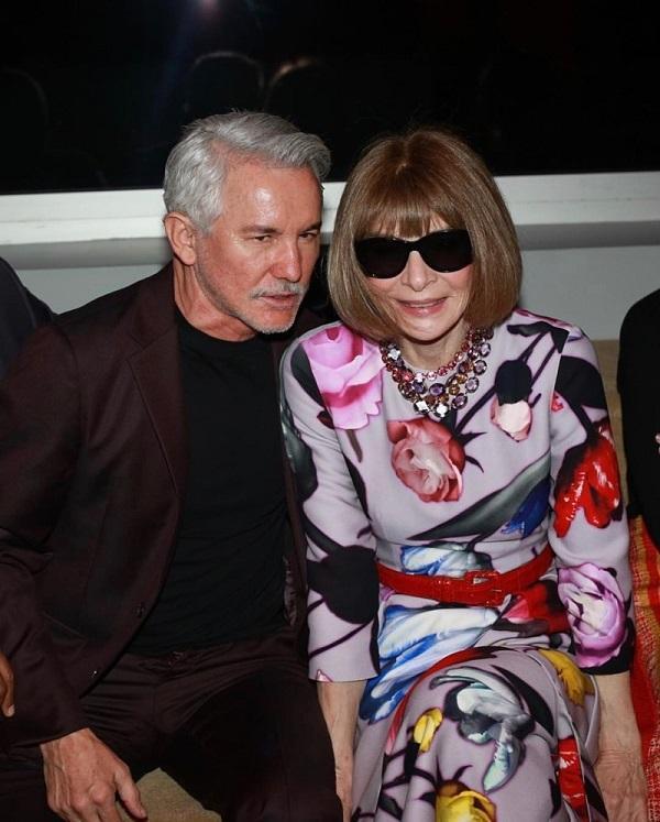 Tổng biên tập Vogue Mỹ Anna Wintour trong chiếc váy họa tiết hoa hồng kín đáo cùng cặp kiếng đen luôn là điểm nhấn, bà ngồi hàng ghế đầu cùng đạo diễn người Úc Baz Luhrmann