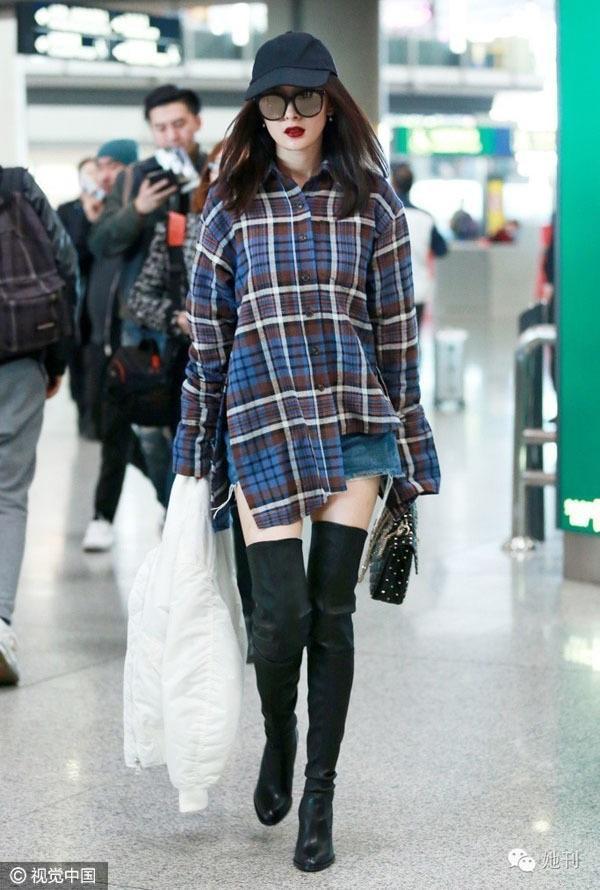 """Dương Mịch trông vô cùng """"chất chơi"""" với áo sơ mi oversized mix cùng boots cao cổ màu đen cùng mũ lưỡi trai khi ra sân bay."""