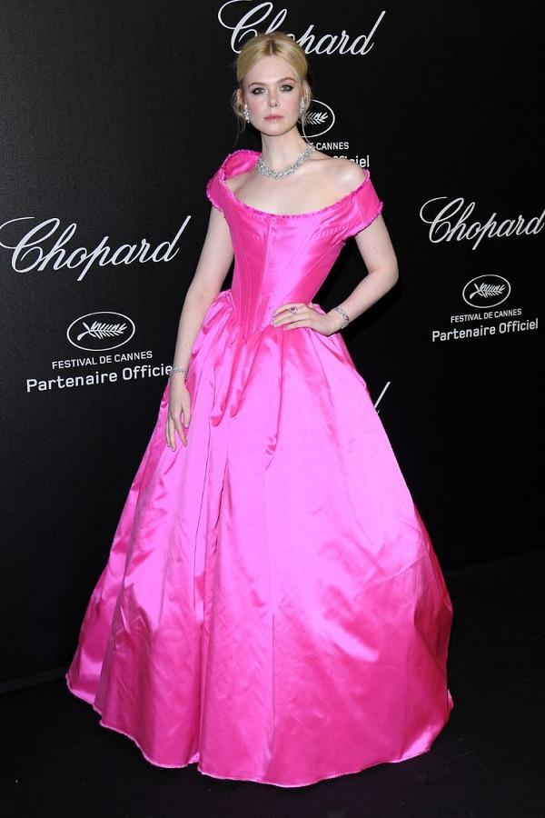 Trong một bữa tiệc khác diễn ra trong khuôn khổ LHP Cannes, Elle Fanning chọn cho mình chiếc váy neon hồng chóe của hãng Vivienne Westwood khoe trọn bờ vai gầy quyến rũ tô điểm trang sức cao cấp, lấp lánh từ Chopard