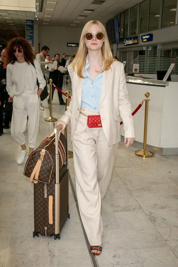 Style sân bay khi đến Pháp với bộ suit thanh lịch màu be mix cùng phụ kiện là túi đeo thắt lưng màu đỏ mini cùng vali hành lý của nhà mốt Louis Vuitton