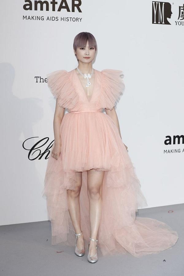 Ca sĩ Lý Vũ Xuân trong thiết kế váy chất liệu voan màu hồng pastel với thiết kế cao-ngắn cùng với phần đuôi váy dài quét đất.