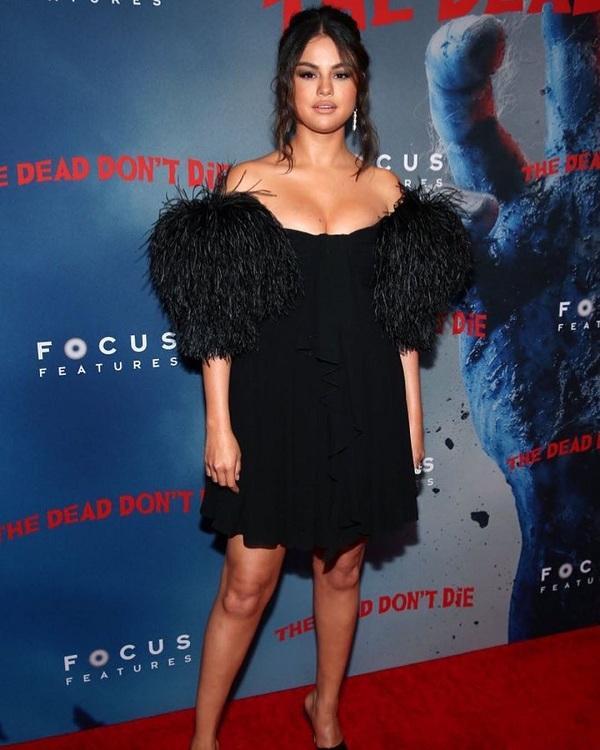 Chiếc váy đen cúp ngực từ nhà mốt Celine nâng vòng 1 căng đầy của Selena tại sự kiện với điểm nhấn tua rua hai bên tay áo