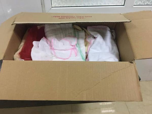 Chiếc thùng giấy nơi để cháu bé kèm một số tã lót.