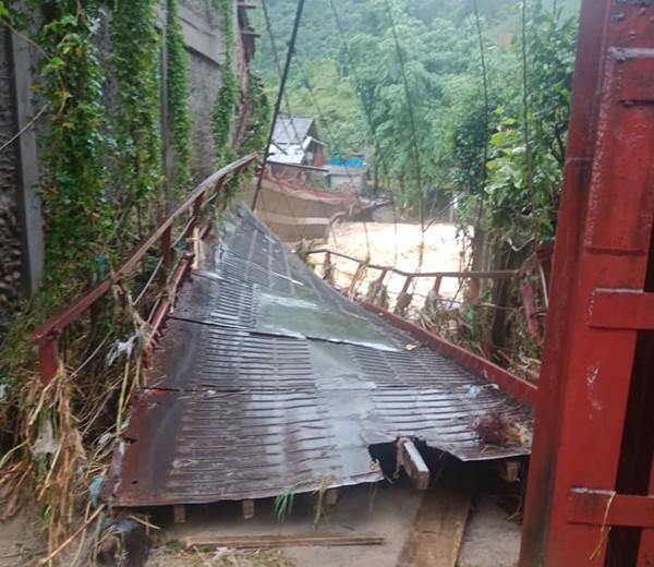 Cây cầu treo nối từ thôn Bản Dền sang thôn La Ve bị lũ cuốn gây hư hỏng.