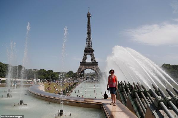 Cục dự báo thời tiết Pháp cho biết, nhiệt độ ở Gallargues-le-Montueux, tỉnh Grad, miền nam đất nước, đạt 45,9 độ C vào 16h20 chiều 28/6. Đây là mức nhiệt nóng nhất từ trước tới nay ở Pháp khi cả châu Âu đang trải qua đợt nắng nóng đầu hè. Trong ảnh, một người phụ nữ tạo dáng chụp ảnh gần nhiều người đang tắm trong Đài phun nước Trocadero gần Tháp Eiffel khi nhiệt độ tăng cao trong suốt mấy ngày qua.