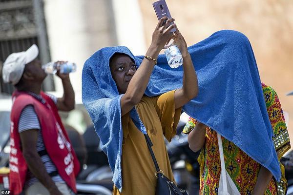 Cũng như Pháp, phần còn lại của châu Âu cũng đang đối mặt với cái nóng đỉnh điểm. Trong ảnh, khách du lịch quấn khăn trên đầu để tránh nóng ởRome, Ý.