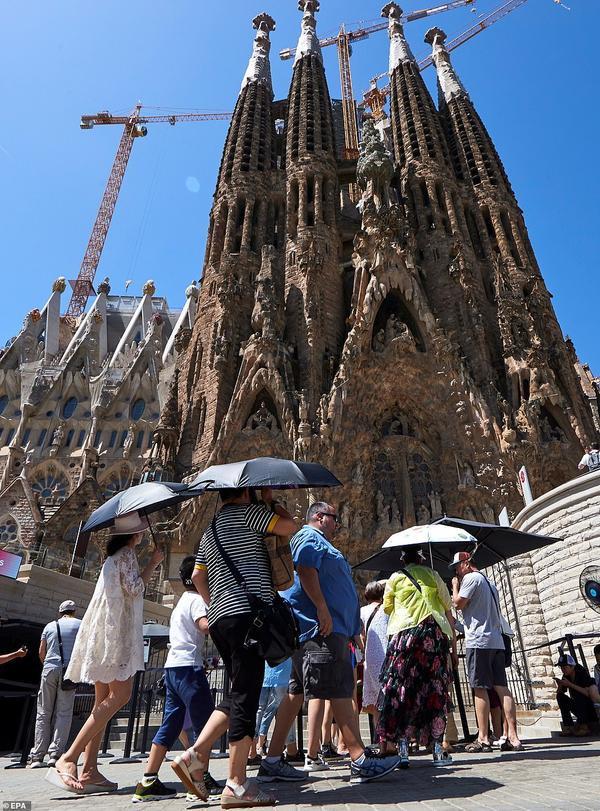 Khách du lịch dùng ô che nắng khi đến thăm thánh đường Sacred Family ở Barcelona, Tây Ban Nha.