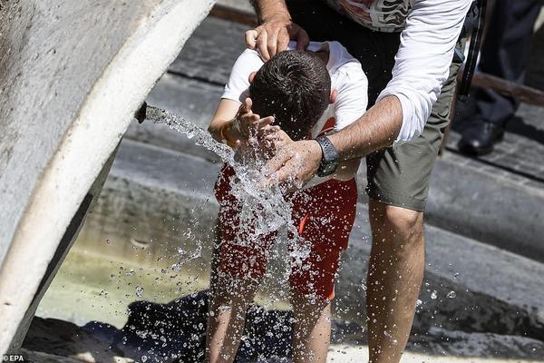 Khách du lịch tá»± làm mát mình trong đài phun nước 'Barcaccia' tại quảng trường Tây Ban Nha ở Rome, Ý.