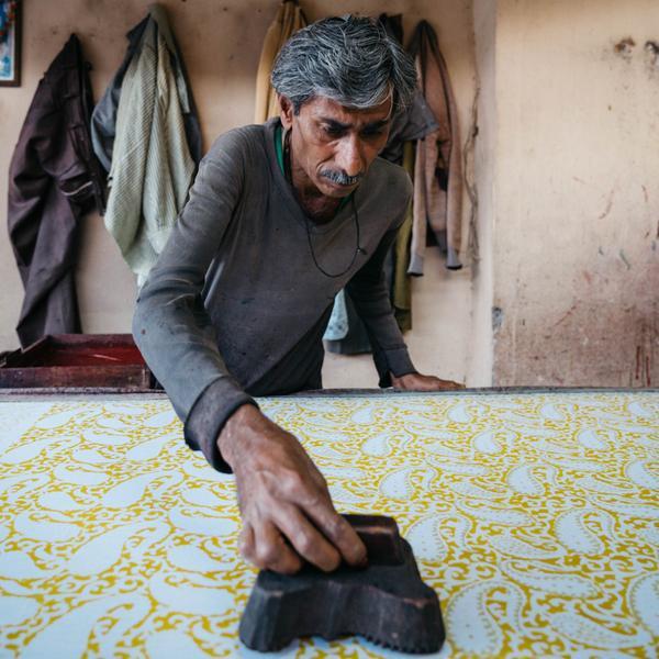 Con dấu được làm từ gỗ đang được dùng để tạo họa tiết cho vải.