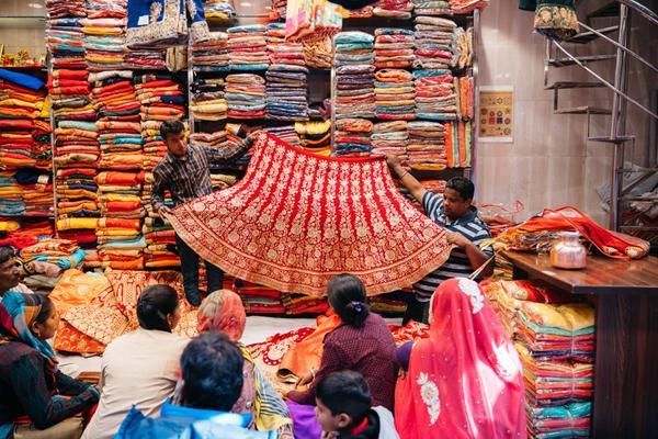 Tại một cửa hàng vải dệt, hai người đàn ông đang chào bán tấm vải cho những người phụ nữ.