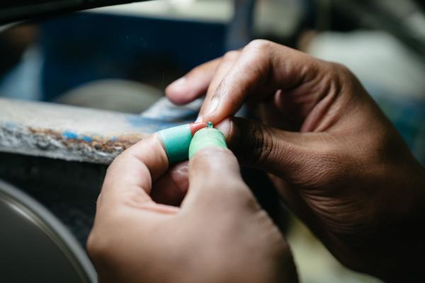 Ngọc lục bảo đang được chuẩn bị để đưa vào máy cắt nhằm tạo ra hình dạng như khuôn rồi bắt đầu đính vào các khung kim loại.