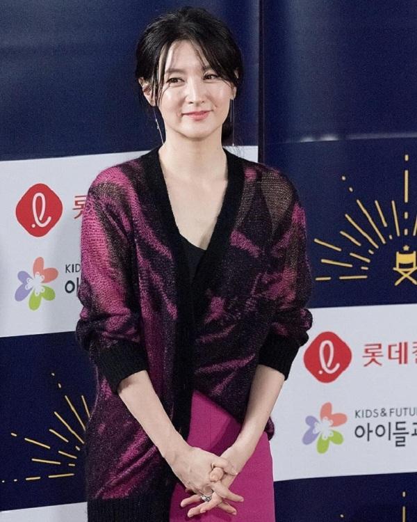 Lee Young Ae chọn trang phục khá bình thường với áo cardigan màu hồng nhạt khoác ngoài bên trong là váy hai dây