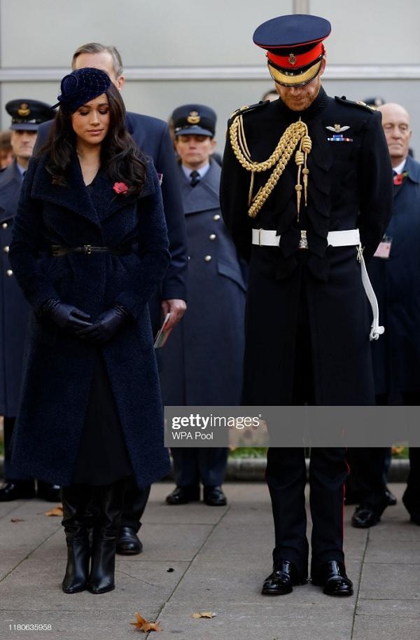 """Meghan chọn cho mình kiểu áo choàng dài xuyệt tông cùng chiếc mũ lưới màu xanh nayvy, kiểu trang phục này đã làm cô trông bị """"dừ"""" hẳn so với người chị dâu xinh đẹp"""
