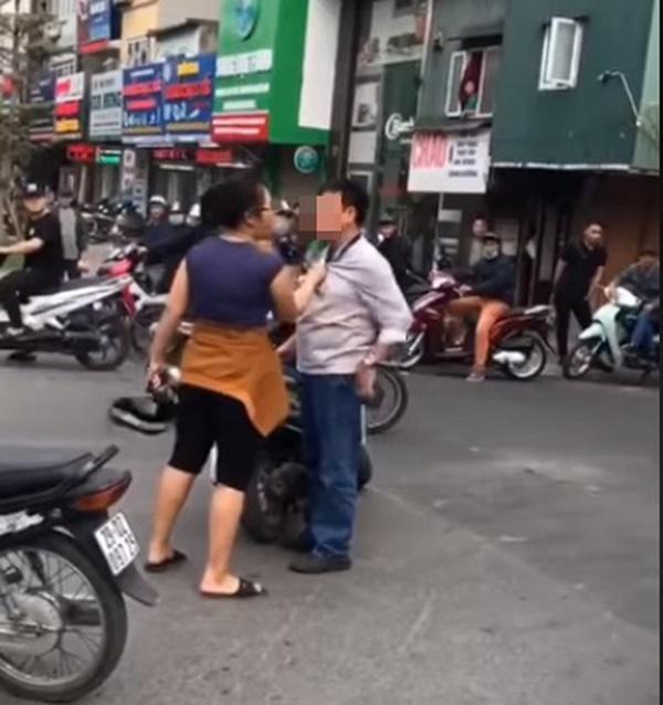 Người phụ nữ tay lăm lăm nón bảo hiểm, tay còn lại nắm cổ áo người đàn ông can ngăn vụ va chạm. Ảnh cắt từ clip