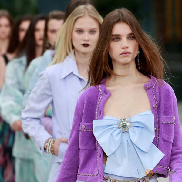 Người mẫu trên sàn diễn Chanel Cruise 2020 với áo khoác tím mix cùng áo croptop kiểu thắt nơ trước ngực