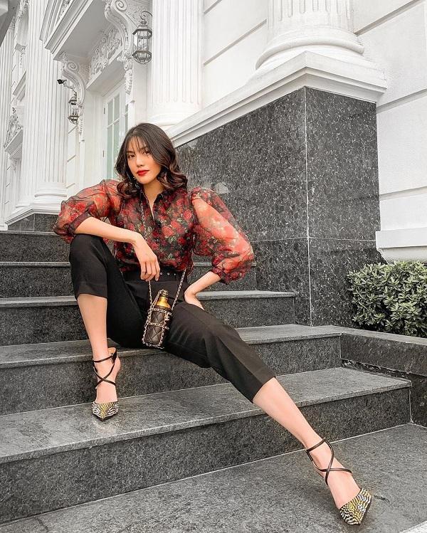 Người đẹp Việt chứng tỏ phong cách sành điệu, đẳng cấp của mình khi có trong tay kiểu túi bình nước của Chanel có giá lên đến mấy trăm triệu đồng. Lan Khuê mix phụ kiện này với áo sơ mi xuyên thấu hoạ tiết hoa cùng quần âu đen tông xuyệt tông màu túi và đôi giày cao gót đinh cá tính