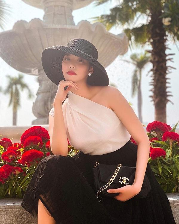 Hình ảnh mới nhất của cô update trên trang cá nhân mang đậm phong cách quý cô sang trọng với kiểu áo trắng lệch vai mix cùng chân váy đen, mũ vành cùng kiểu túi xách Chanel 19 Flap Bag