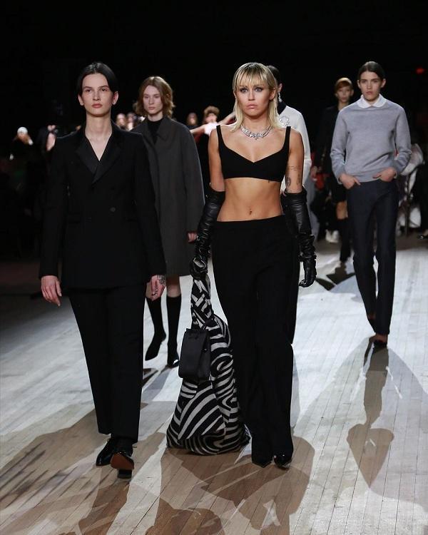 Nữ ca sĩ mặc bra top đen khoe cơ bụng săn chắc mix cùng quần kaki đen dài với phụ kiện găng tay da và phụ kiện trang sức lấp lánh trên cổ