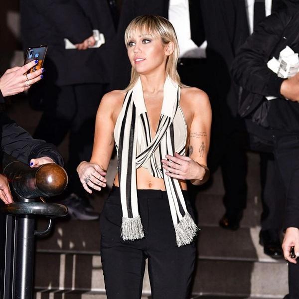 Miley Cyrus xuất hiện đầy nổi bật với tư cách là khách mời VIP và là model sải bước trong show, kiểu áo sọc đen trắng trông như chiếc khăn choàng khoác hờ mix cùng quần đen ôm sát rạt thân hình