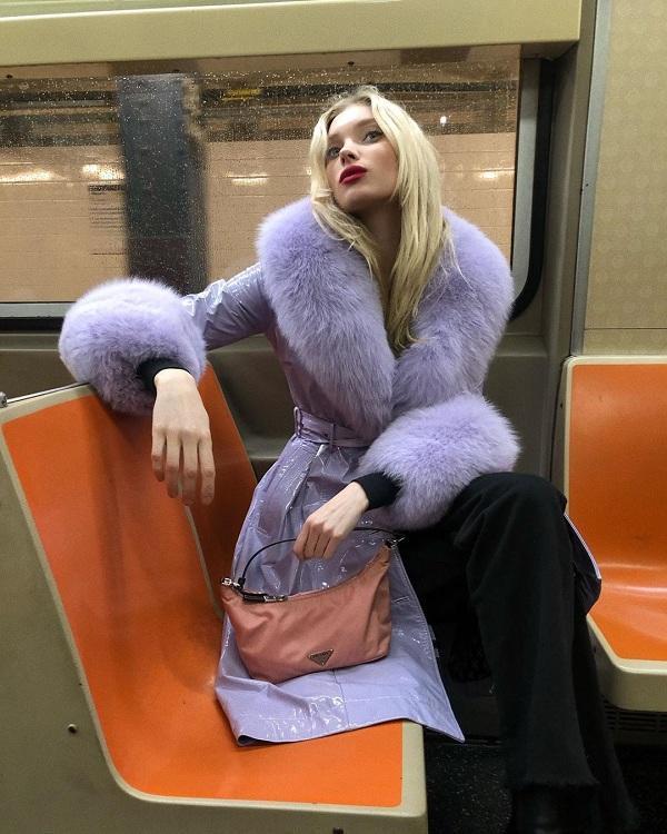 Thiên thần nội y Elsa Hosk khoác áo măng tô tím lông vĩ mix cùng quần đen và chiếc túi xách mini màu hồng