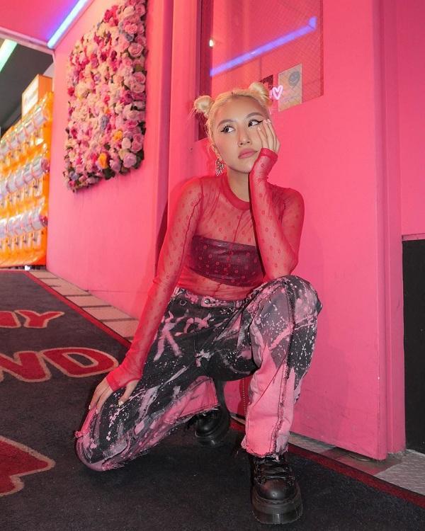 Quỳnh Anh Shyn trong thiết kế áo sheer neon màu hồng, cô nàng mặc áo quây đen bên trong mix cùng dáng quần chất liệu ombre hồng mix cùng giày bốt cá tính