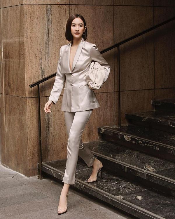 Á hậu Hà Thu trong bộ cánh thanh lịch với suit màu xám bạc xẻ ngực mix cùng phụ kiện túi Pouch Bag