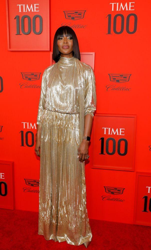 Báo đen Naomi Campbell xuất hiện trong chiếc váy màu vàng óng ánh cùng kiểu tóc cleopatra.