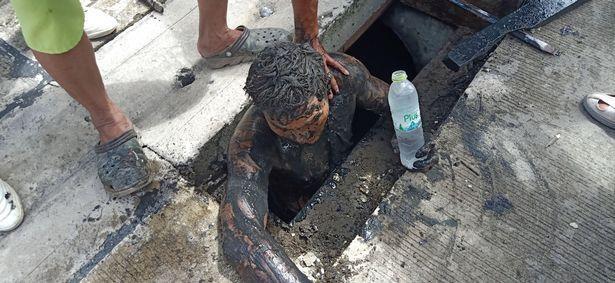 Người dân đưa nước cho tên tội phạm trốn dưới cống.