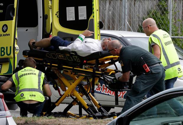 Nhân viên y tế đưa nạn nhân vụ xả súng lên xe cứu thương. Ảnh: AP