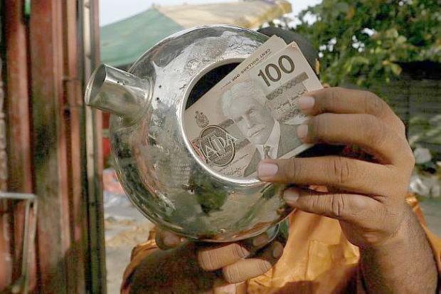 Chiếc ấm chứa đầy tiền đôla Canada.