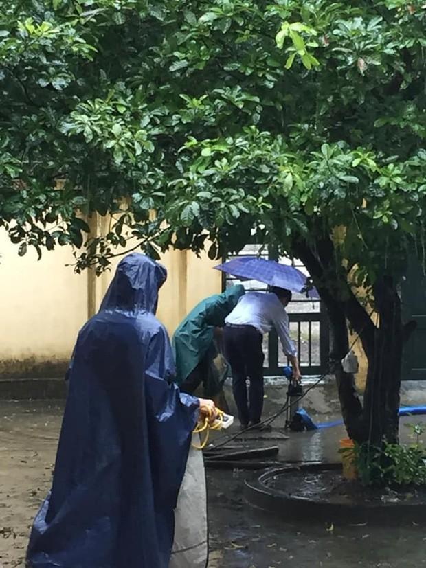 Thầy hiệu trưởng (áo trắng) dầm mưa giúp các bạn học sinh sửa ống thoát nước để sân trường bớt ngập nước.