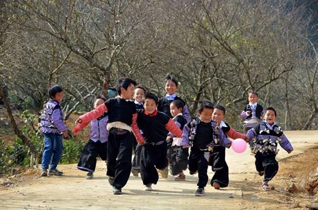 Trẻ em tung tăng đi chơi Tết trong trang phục truyền thống sặc sỡ. (Ảnh: Thanh Hà/TTXVN)