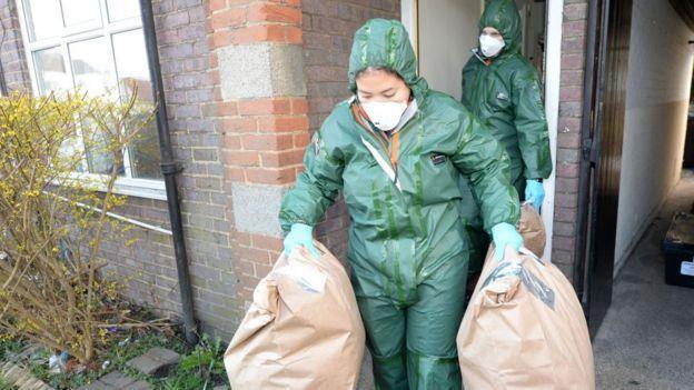 Cảnh sát Anh khuân các bao chứa cần sa ra từ một căn nhà bị biến thành trang trại cần sa.