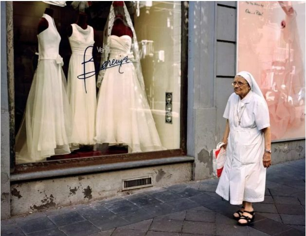 Một nữ tu sĩ già trước tiệm váy cô dâu tại khu phố phía Nam Naples