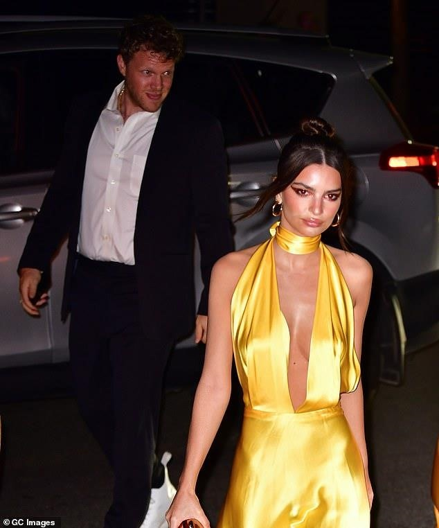 Emily Ratajowski lả lơi trong chiếc váy vàng xẻ sâu tận rốn.