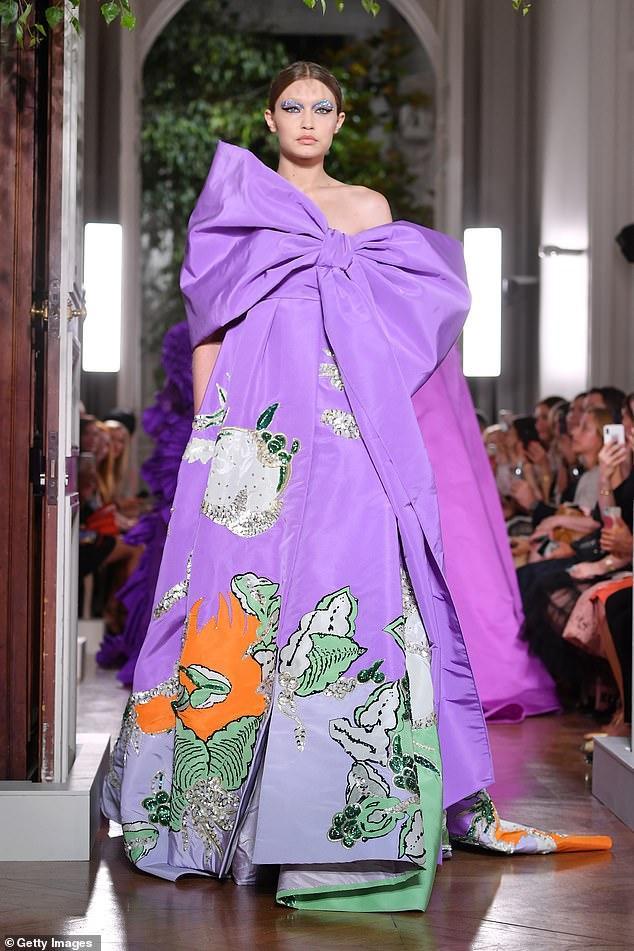 Trong show của nhà mốt Ý còn có sự góp mặt của siêu mẫu Gigi Hadid trong thiết kế váy tím có bản nơ to trước ngực cùng tông makeup nhấn đậm phần mắt lạ lẫm.