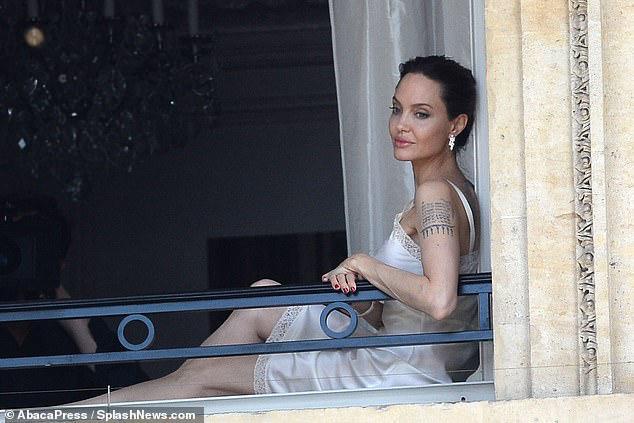 Vợ cũ của Brad Pitt thả dáng quyến rũ trong chiếc váy ngủ trắng tinh khôi tại ban công trong một cảnh quay cho hãng nước hoa
