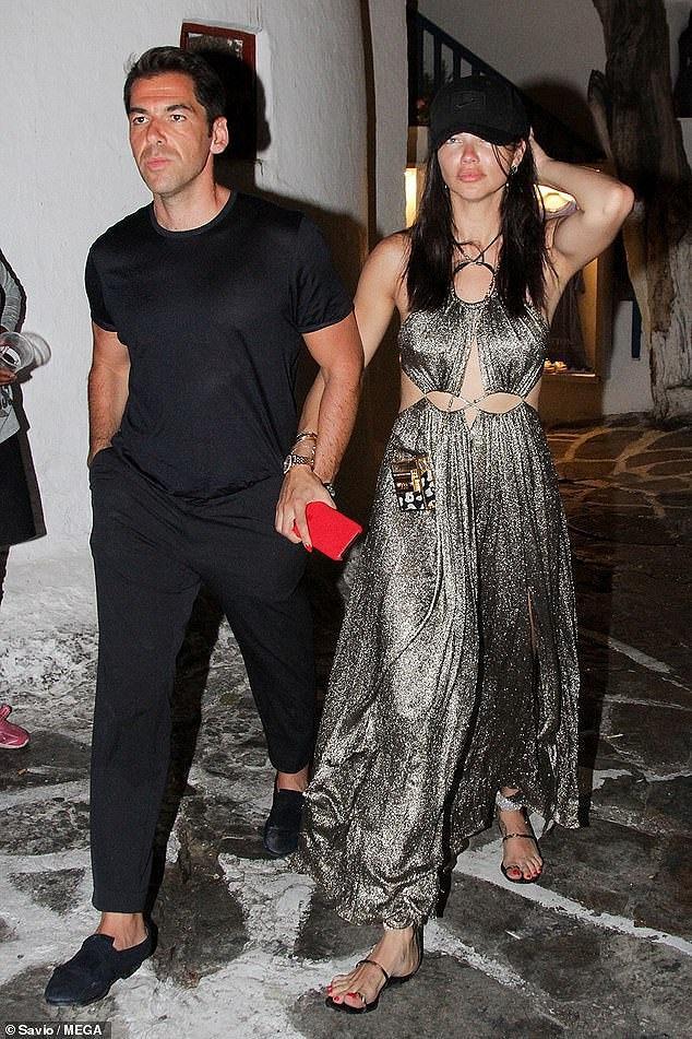 Cựu thiên thần nội y Adriana Lima mặc bộ váy maxi chất liệu sequin mix cùng giày sandals bệt , đội mũ lưỡi trai tay trong tay cùng bạn trai mới