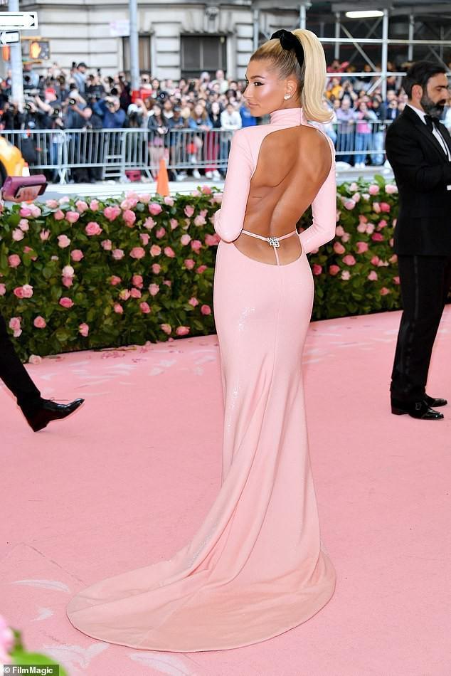 """Tại Met Gala 2019 năm nay, chân dài Hailey Bieber đã biến mình như một nàng búp bê Barbie với mái tóc vàng buộc cao cùng chiếc váy hở khoe trọn lưng trần với điểm nhấn quần lót dây màu hồng """"matching"""" với trang phục thu hút bao ánh nhìn"""