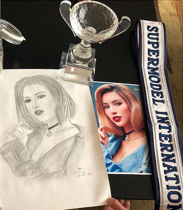 """Siêu mẫu quốc tế Khả Trang khoe tranh vẽ fan tặng cùng """"chiến tích"""" mà cô nàng nhận được khi đăng quang ngôi vị quán quân Supermodel International 2018 tại Thái Lan."""