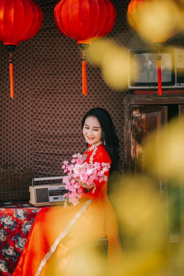 """""""Vợ sắp cưới"""" của Tiến Linh lại trung thành với sắc đỏ truyền thống của áo dài Việt Nam. Ngọc Quyên còn điệu đà với cành mai trên tay cùng nụ cười tươi tắn."""